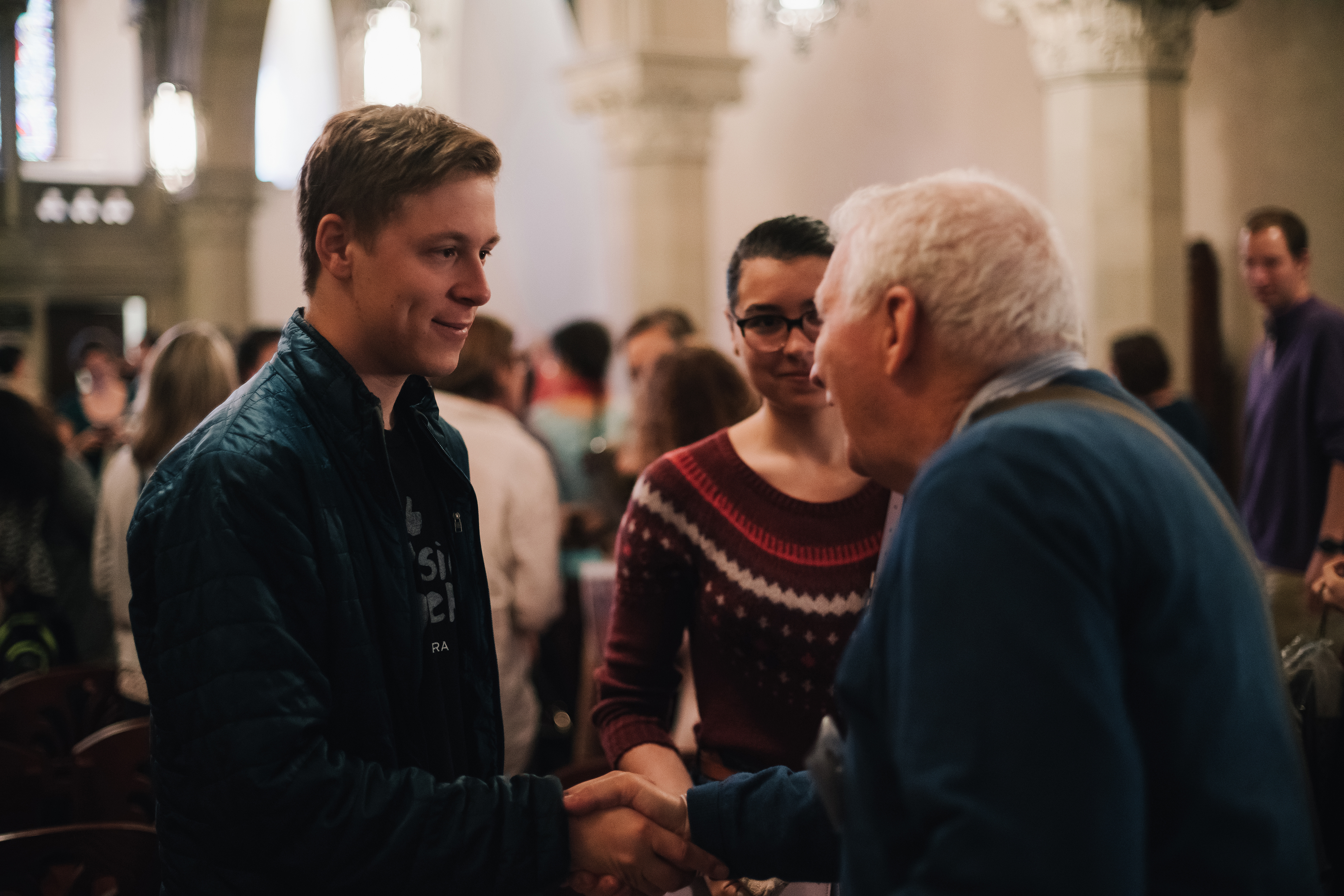 A young man and an older man greet each other and shake hands during Jazz Worship at Old South Church